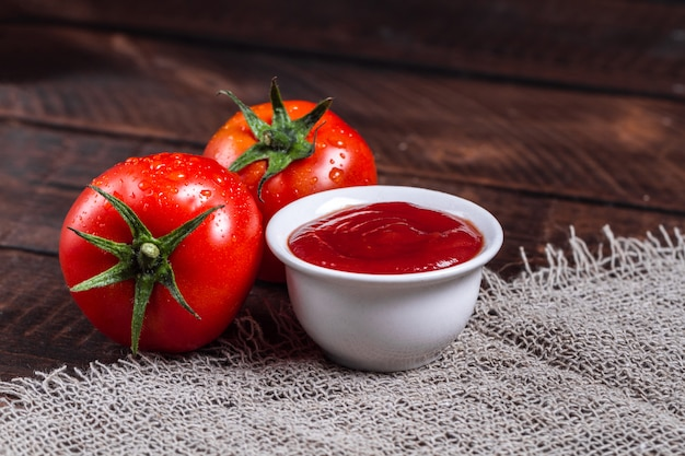 Red tomatoes and tomato sauce on a dark, wooden background.