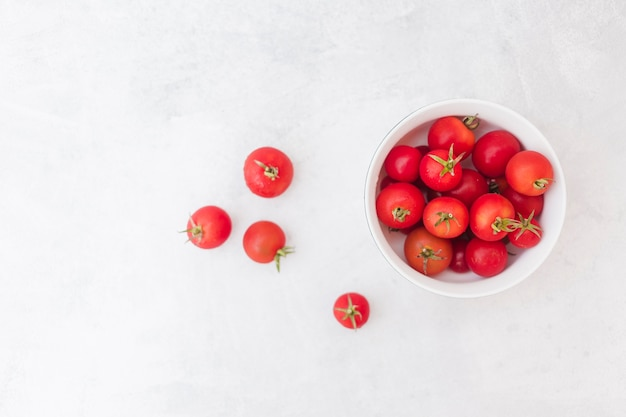 Red tomatoes in white bowl on white textured background