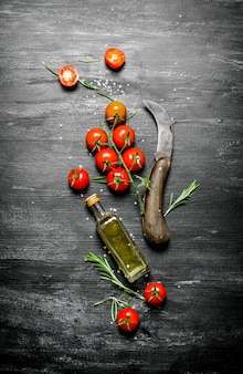 ローズマリーとオリーブオイルのボトルと赤いトマト。黒の素朴な背景に。