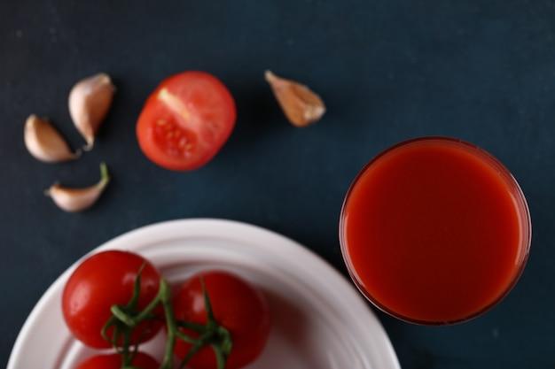 Красные помидоры с водой посыпать на них в белой тарелке со стаканом сока. вид сверху.