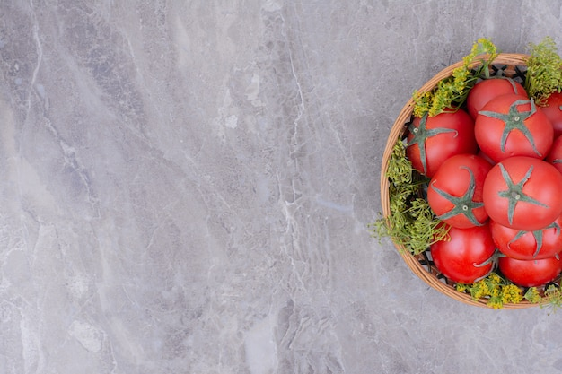 Red tomatoes in a wooden platter on marble.