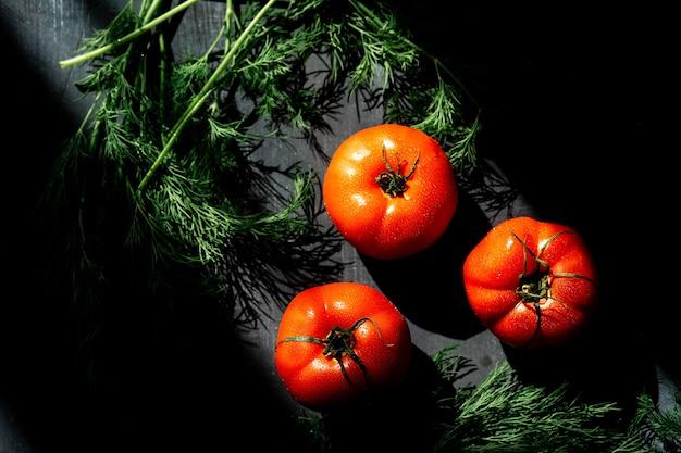 Красные помидоры на черной сервировочной доске на темном фоне. в лучах счета