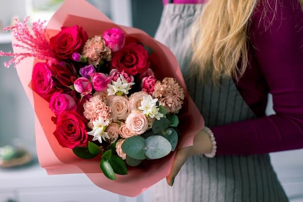 붉은 색조 여자 손에 혼합 된 꽃의 아름 다운 꽃다발입니다. 꽃집에서 꽃집의 일. 잘 생긴 신선한 꽃다발. 꽃 배달.