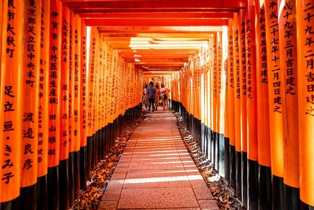 観光客や日本人学生がいる伏見稲荷大社の赤い鳥居