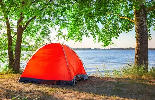 Красная туристическая палатка на озере летом