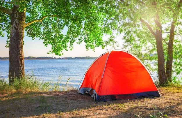 Красная туристическая палатка на озере под ярким солнцем летом