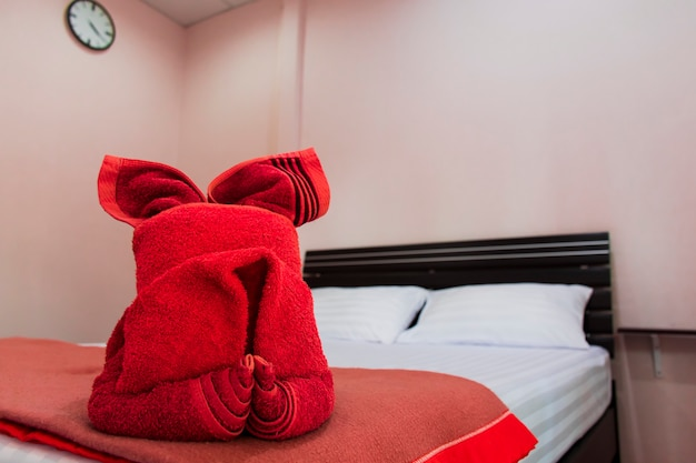 A red towel folded in a cartoon character is placed on the bed.