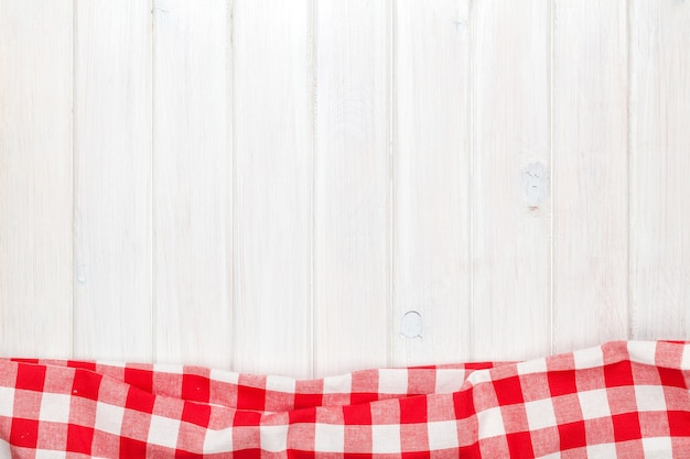 Красное полотенце над деревянным кухонным столом. вид сверху с копией пространства