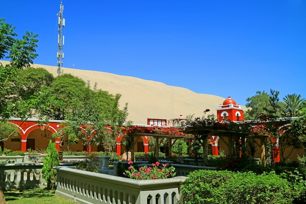 Red tower of vintage peruvian building against the sand dunes of huacachina desert, ica region, peru