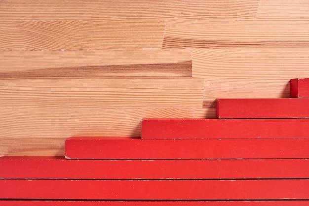 Красные блоки игрушки заделывают на деревянном столе.