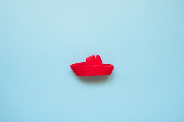 Red toy boat on blue sea copy space. beach vacation concept