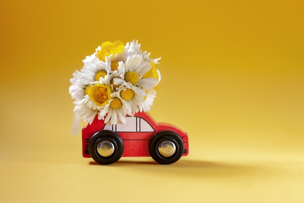 Red toy car delivering bouquet of flowers box on yellow. flower delivery.