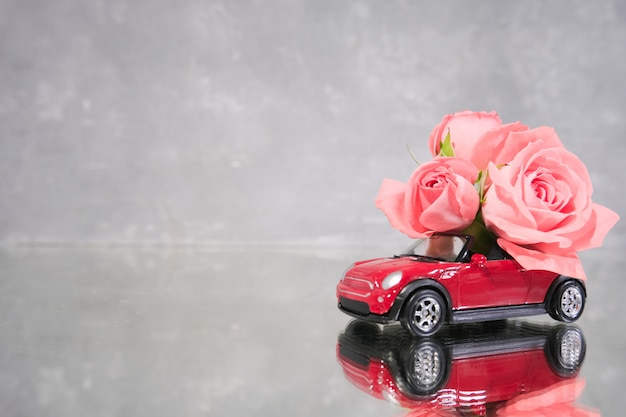 Red toy car delivering bouquet of pink rose flowers on grey background.