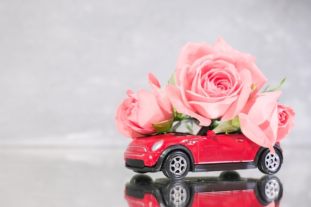 Red toy car delivering bouquet of pink rose flowers