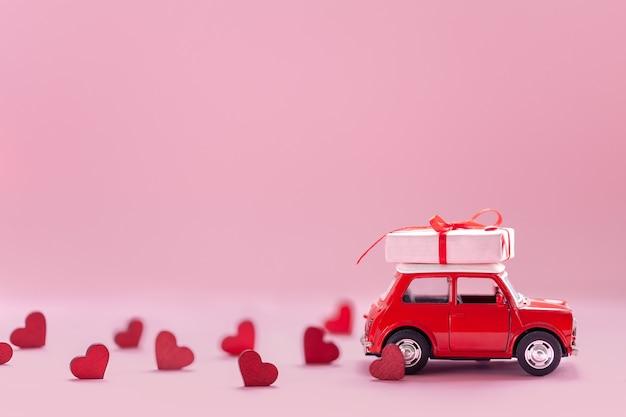 ピンクの壁に小さな赤いハートが付いた屋根のギフトボックスを運ぶ赤いおもちゃの車。