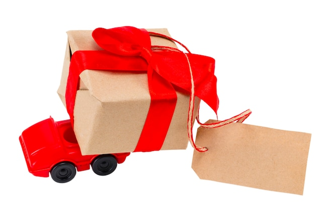 Red toy car delivering gifts box with tag with empty space for a text on a white background.