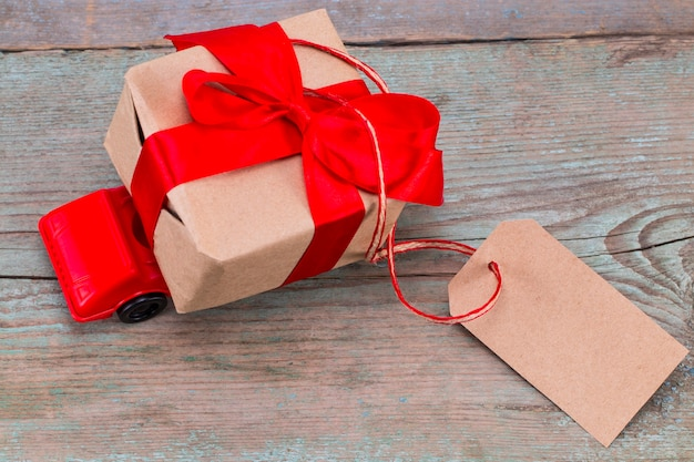 Red toy car delivering gifts box with tag with empty space for a text on wooden background.