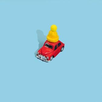 青い背景の黄色の冬の帽子の赤いおもちゃの車