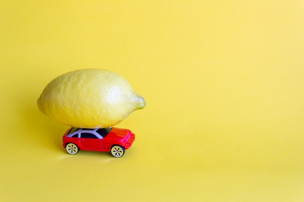 Red toy car lucky with fresh lemon, citrus delivery