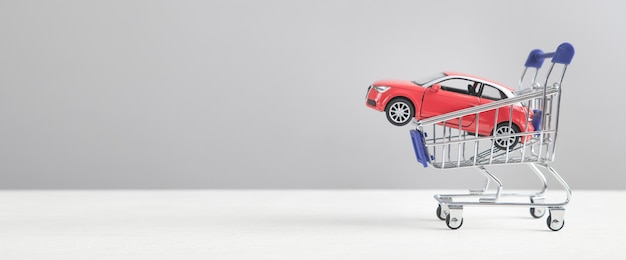 Red toy car in shopping cart.