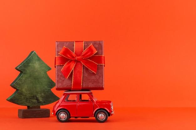 屋根の上のクリスマスツリーとギフトボックスが付いている赤いおもちゃの車