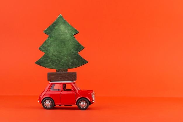 屋根の上のクリスマスツリーと赤いおもちゃの車