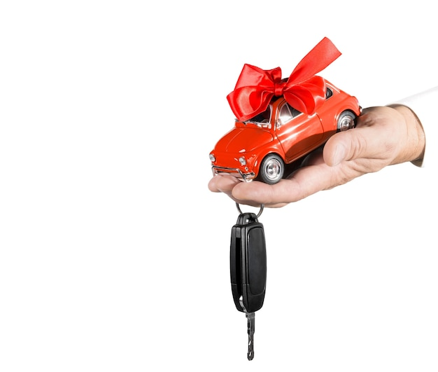 활과 흰색 배경에 고립 된 남성 손에 키 빨간 장난감 자동차. 자동차 구매 개념