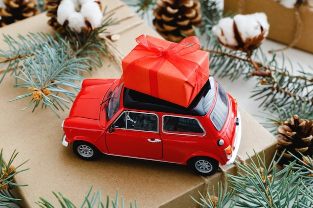 Red toy car with christmas red gift box