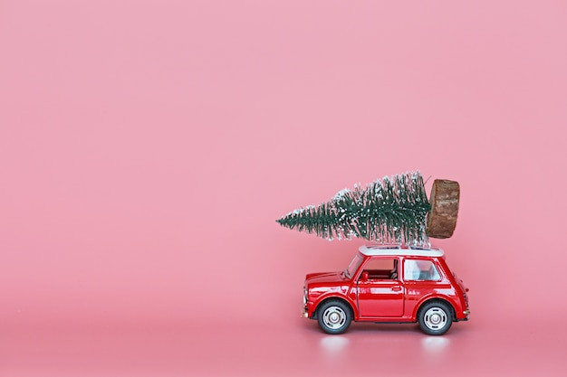 Red toy car with a christmas tree on the roof on pink