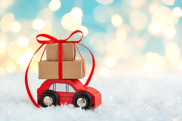 Red toy car with stack of christmas gift boxes