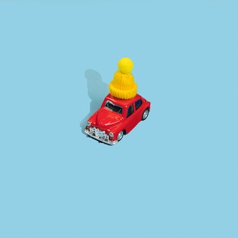 Red toy car in yellow winter cap on blue background