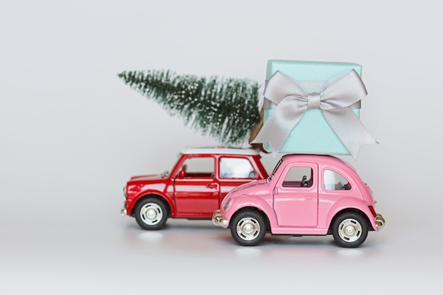 Red toy cars with christmas tree and gift box on roof on white