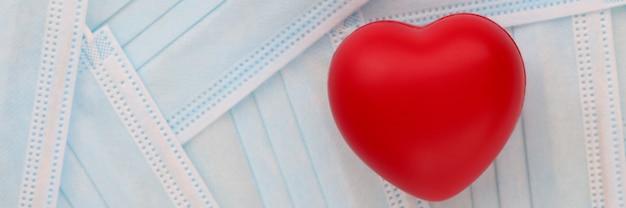 Красное игрушечное сердце, лежащее на столе среди медицинских защитных масок в клинике. осложнение концепции covid-19 сердечно-сосудистой системы
