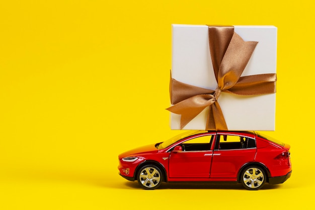 Red toy model car with present gift box on the top on yellow