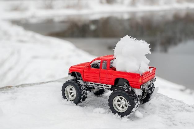 빨간색 장난감 픽업 트럭은 푹신한 눈덩이를 등에 실었습니다. 겨울 야외 활동