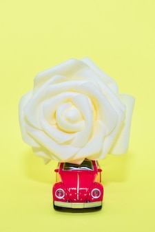 Red toy retro car carries large white rose on roof. flower delivery concept, valentine, postcard