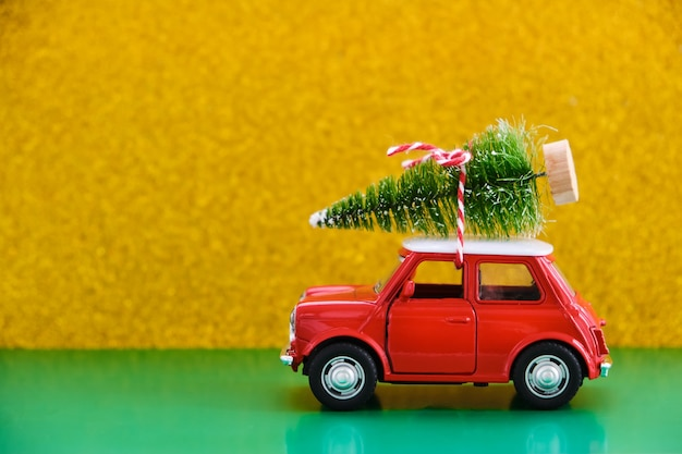 Red toy retro car delivering a gift on green-yellow
