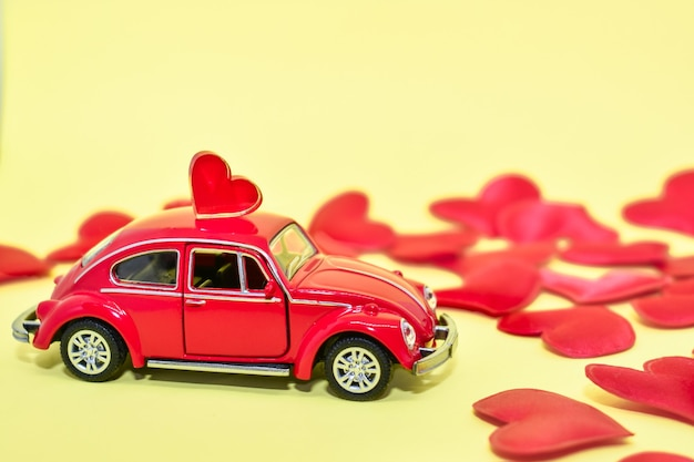 Red toy retro car with hearts on yellow background. scattered hearts and car. valentine, postcard