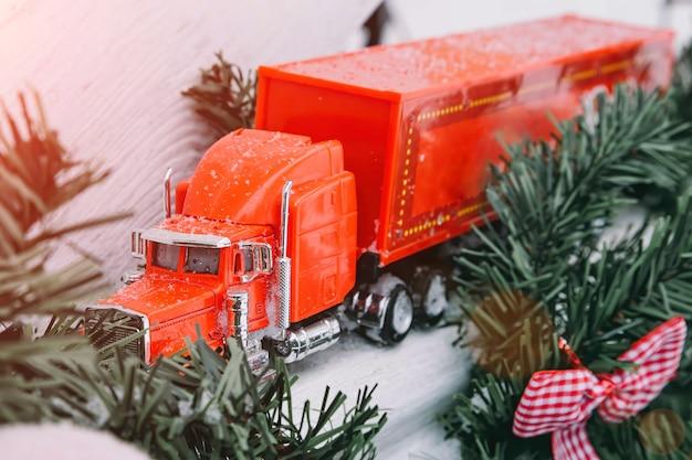 赤いおもちゃのトラックと新年のdecorationstruckは、木製のランプにクリスマスツリーに乗るギフトをもたらします