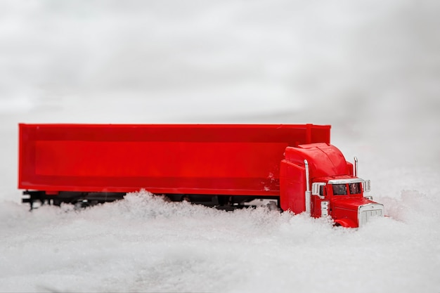 빨간 장난감 트럭은 눈 덮인 도로에서 겨울에 타고 눈 더미가 오는 휴가를 통과합니다.