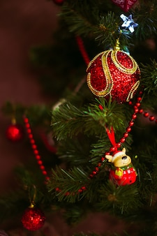 Red toys hang on a christmas tree