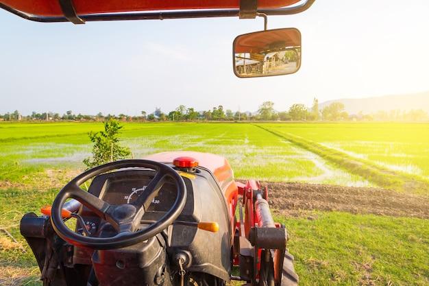 화창한 여름날에 농업 분야에 빨간 트랙터