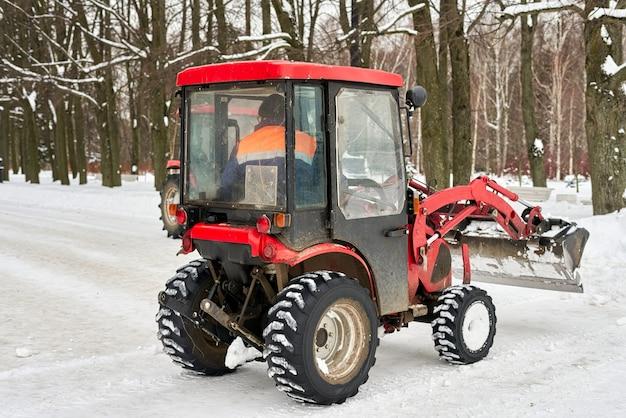 雪のバケツが付いた赤いトラクターが公園を掃除します