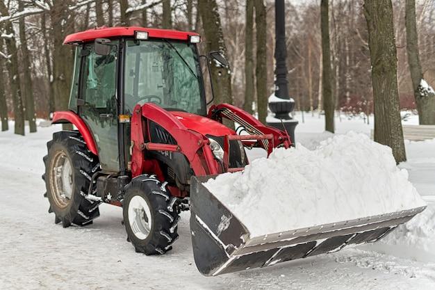 Красный трактор с большим ковшом убирает снег в городском парке. закрыть вверх