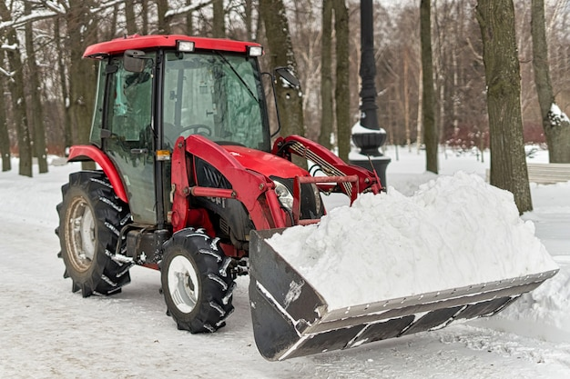 Red tractor with a large bucket removes snow in a city park. close up