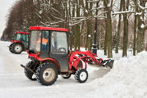 Red tractor with a large bucket removes snow in a city park
