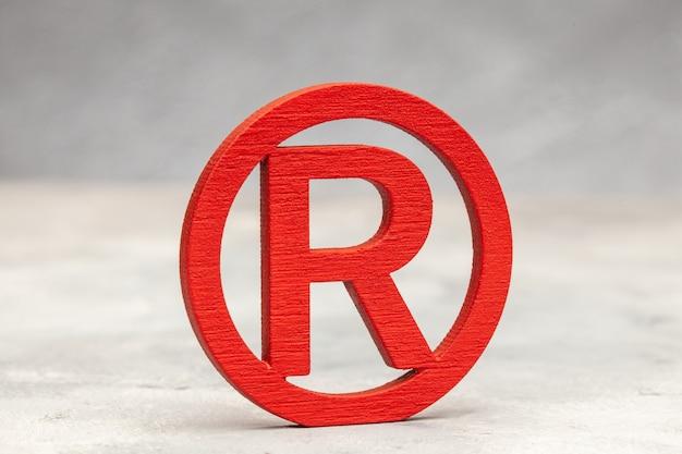 Красный знак торговой марки на серой поверхности.