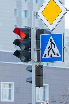 Red traffic light, pedestrian crosswalk and main road traffic signs