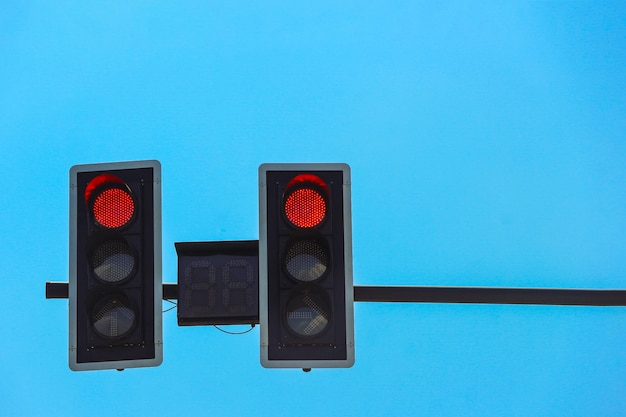 Red traffic light with clear blue sky as background.