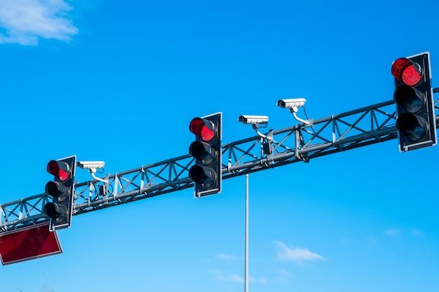 赤い信号機とカメラが青い空を再び照らす
